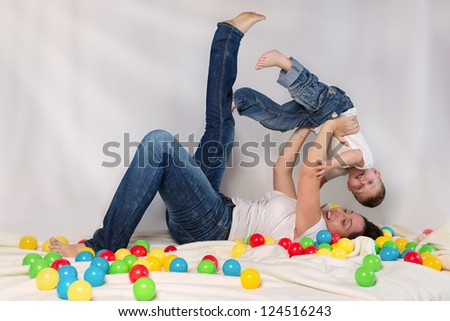 Mother playing with his son among colorful balls - stock photo