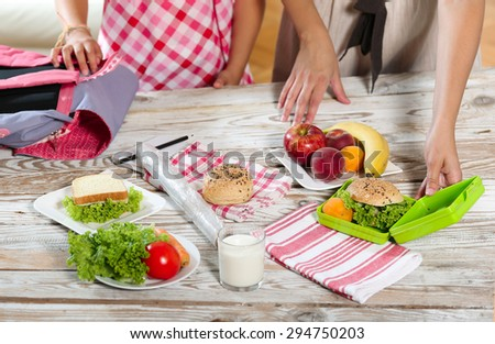 Mother preparing healthy and tasty lunch box for child - stock photo