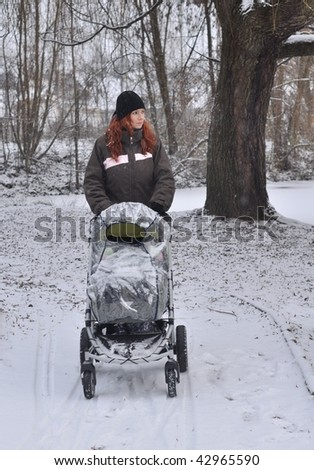 mother with baby carriage. winter - stock photo