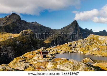 Mountain hut hidden in the heart of Lofoten wild ridge, Norway, Hermannsdalstinden summit in the background - stock photo