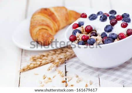 Muesli with yogurt  and berri,cowberry  bilberry with tasty croissant - stock photo