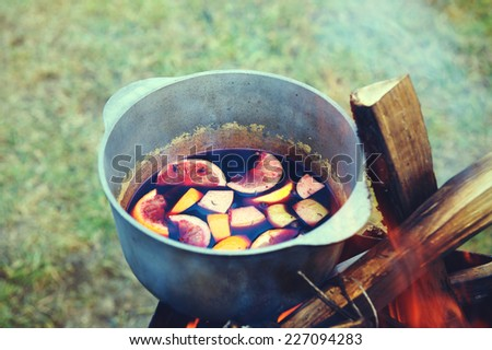 Mulled wine in a tourist pot over hot camp fire - stock photo
