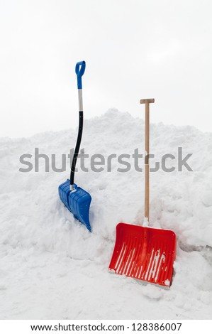 Multicolored snow shovels in snow pile - stock photo