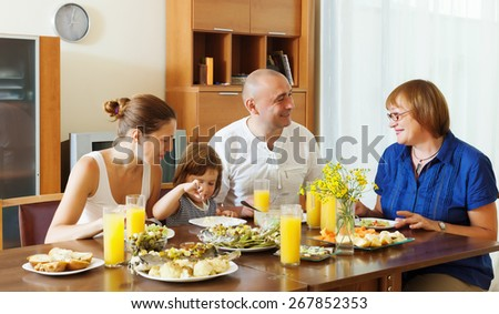 multigeneration family  eating fish with vegetables at home together - stock photo