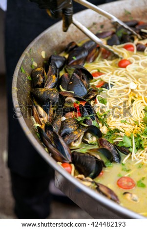 Mussels cooked with white and red wine sauce and spaghette at mussels festival - stock photo