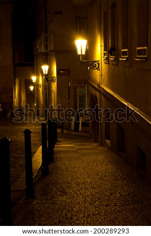 Narrow alley with lanterns in Prague at night ,  Czech Republic . - stock photo