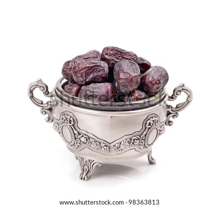 Natural dates in a metal container isolated white background - stock photo
