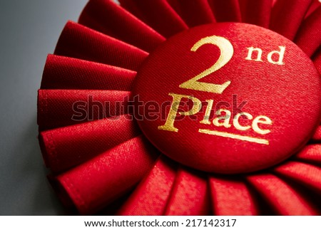 2nd place winners rosette in red with gold text made of pleated ribbon to be awarded to the runner up in a competition, close up view - stock photo