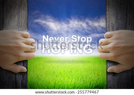 """""""Never Stop Hoping"""" Motivational quotes. Hands opening a wooden door then found a texts floating among new world as green grass field, Blue sky and the Sunrise. - stock photo"""