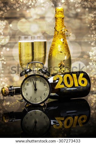 2016 New Year concept with the date in numbers, clock and bottle of champagne - stock photo