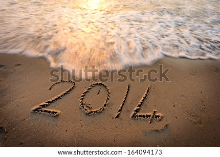 New Year 2014 Engraved on Beach Sand - Oncoming Waves - stock photo