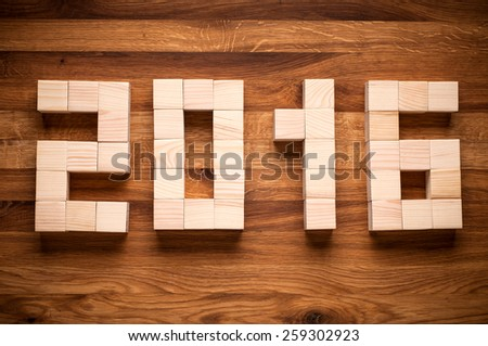 2016 New Year in shape from wooden cubes on wooden background. - stock photo