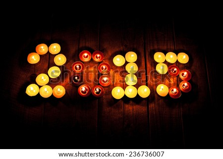 2015 new year. Many beautiful small candle on an old wooden vintage background. Burning candles in the form of numbers - stock photo