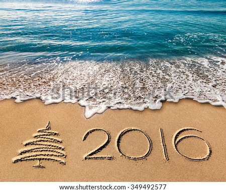 new year 2016 written in sand  sea and blue sky - stock photo