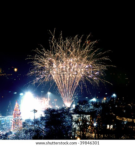 2014 New Years party with huge fireworks in a public square with a huge christmas tree - stock photo
