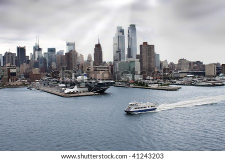 New York skyline and sea, air, space museum with an aircraft carrier along the shore of the Hudson river under dark grey skies - stock photo