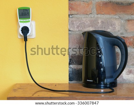 NICA, LATVIA - NOVEMBER 6, 2015: Electric teapot is connected with socket through digital electricity consumption meter for energy saving.       - stock photo