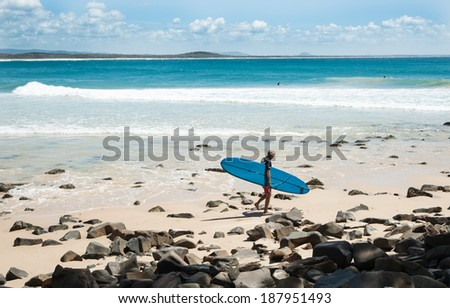 NOOSA, AUSTRALIA - MARCH 11; Surfer carrying a blue long-board heads to the water to complete in the Noosa Festival of Surf on March 11, 2014 at Noosa, Australia.  - stock photo