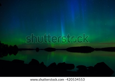 Northern lights dancing over calm lake (Aurora borealis) - stock photo