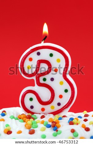 Number three birthday candle on red background - stock photo