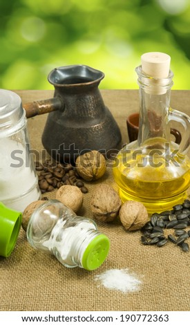 nuts, seeds,butter, salt shaker, coffee beans, a cup on a green background closeup - stock photo