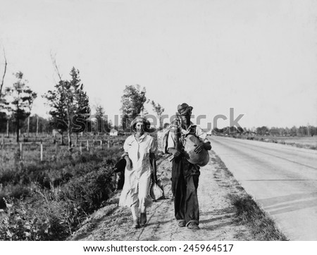 'Oakies' couple migrating. Cotton workers on the road carrying all they possess as they say 'Damned if we'll work for what they pay folks hereabouts.' Crittenden County Arkansas May 1936. - stock photo
