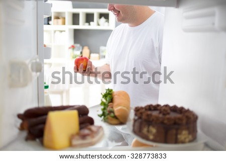 Obese man take apple from fridge instead of high calorie meal from fridge