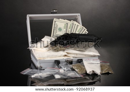 ?ocaine and marijuana with gun in a suitcase on grey background - stock photo
