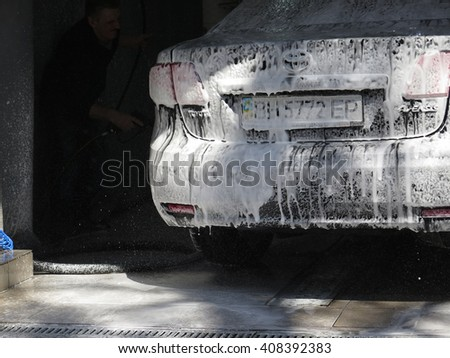 Odessa, Ukraine, April 18, 2016 - man washing his car on a bright sunny day in the garage cleaning in the city center.                         - stock photo