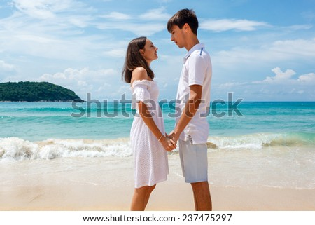 of a young romantic couple on a beach looking at each other - stock photo