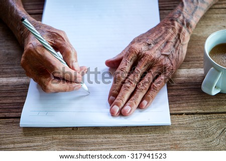 old man writing with a pencil in a notebook,Handwriting - stock photo