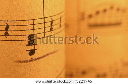 ...old print..close up of sheet music with warm lighting. - stock photo
