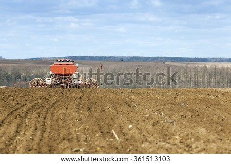 old tractor yielding wheat in the spring season. - stock photo