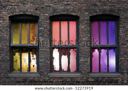 3 old weathered windows with backlight during sunset - stock photo