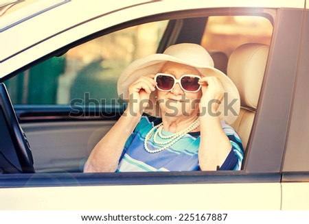 old woman in sunglasses sitting in the car . - stock photo
