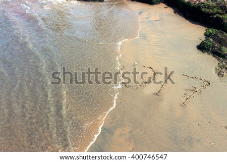 2017 on a beach sand, the wave is covering digits 2017. This year will be end soon. - stock photo