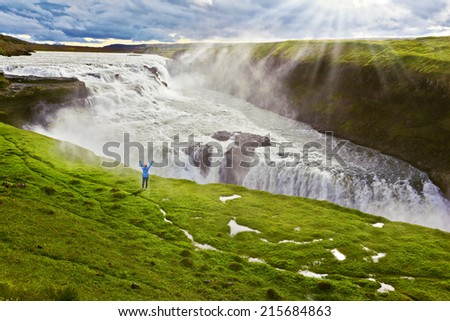 On a mountain slope the woman delighted looks at a boiling chasm. Powerful Gullfoss in Iceland.  - stock photo