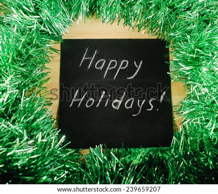 "on the black Board, white chalk written ""happy nholidays"" on the background of green tinsel. - stock photo"