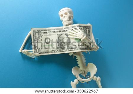 one dollar in skeleton fingers  - stock photo