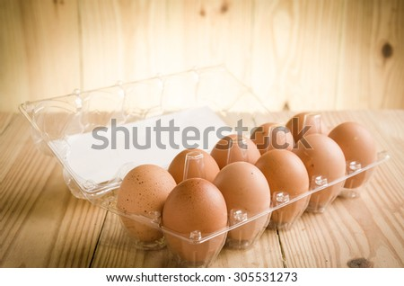 One dozen farm fresh eggs photographed on a wood table - stock photo