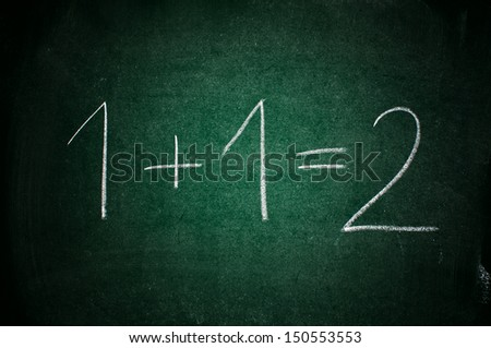 """""""One plus one equals two"""" written in chalk on a green chalkboard - stock photo"""