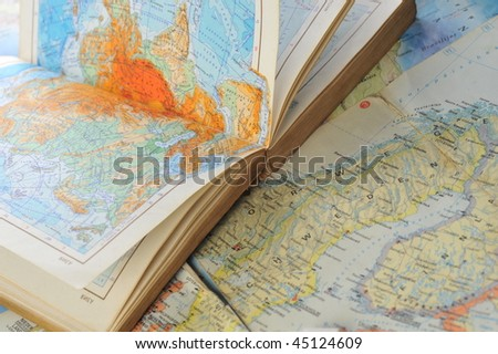 opened old atlas book on  map - stock photo