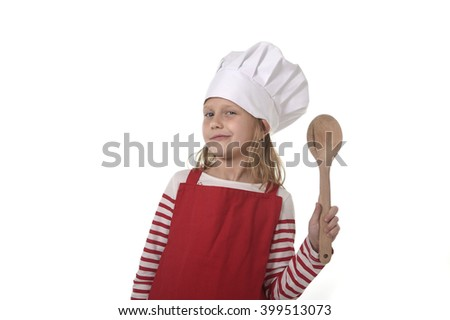 6 or 7 years old little girl in cooking hat and red apron playing cook smiling  happy holding spoon isolated on white background looking excited - stock photo