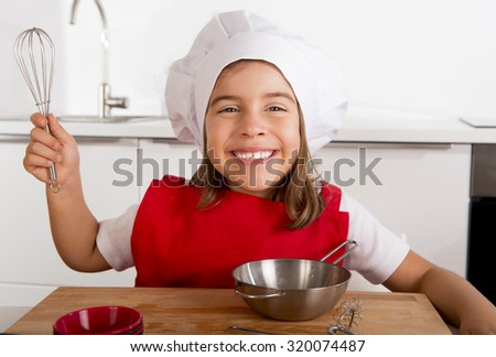 4 or 5 years old sweet little girl in red apron and cook hat playing chef learning cooking at home kitchen smiling happy - stock photo