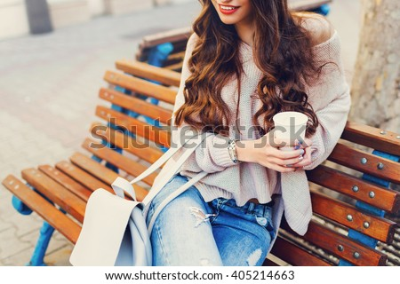 Outdoor fashion details. Sunny lifestyle  image of   stylish young  attractive woman in cozy knitted sweater  , holding cup of  hot  beverage , sitting on wooden  city bench. - stock photo