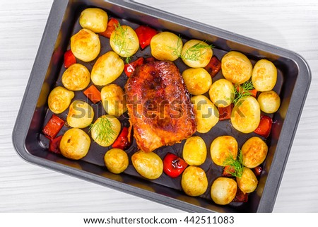 Oven Baked new potatoes with sea salt, red bell pepper and pork tenderloin in a baking dish, on a wooden table, close-up - stock photo
