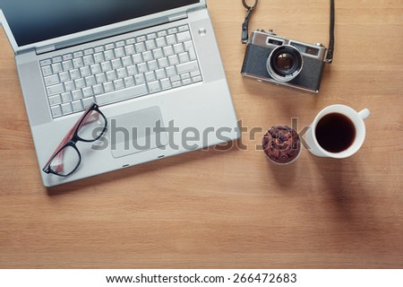 Overhead of modern comfort work place. Different objects on wooden background. Items include camera, glasses, laptop, cup of coffee and muffin - stock photo