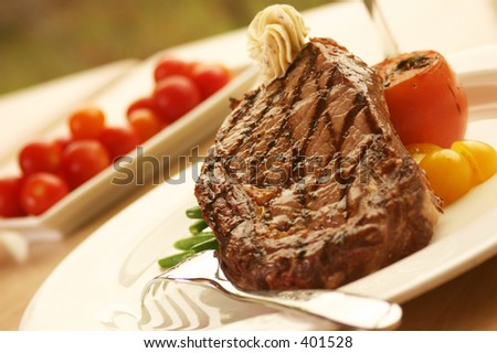 12oz ribeye steak topped with truffle butter and grilled tomato - stock photo