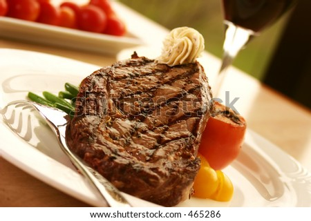 12oz ribeye steak topped with truffle butter and grilled tomato. Served with red wine. Shallow DOF - stock photo