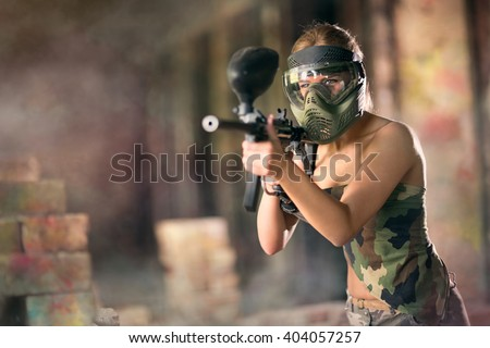 Paintball, female player with marker gun  - stock photo